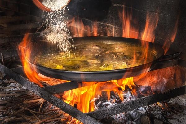 adding rice into big iron pan