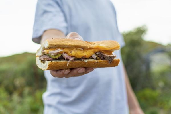 a man holding a steak sandwich