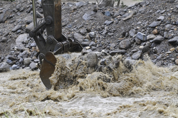 regulating water stream with excavator for