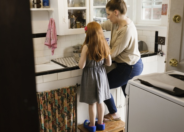 girl and mother baking together in