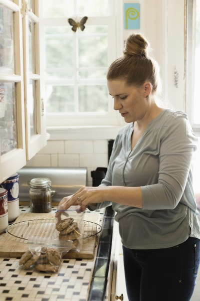 mid adult woman putting biscuits into