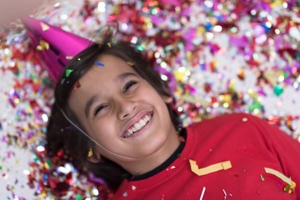 kid blowing confetti while lying on