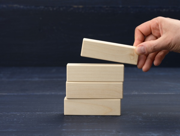 female hand puts wooden blocks on