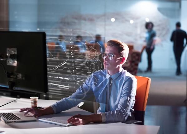 man working on computer in dark
