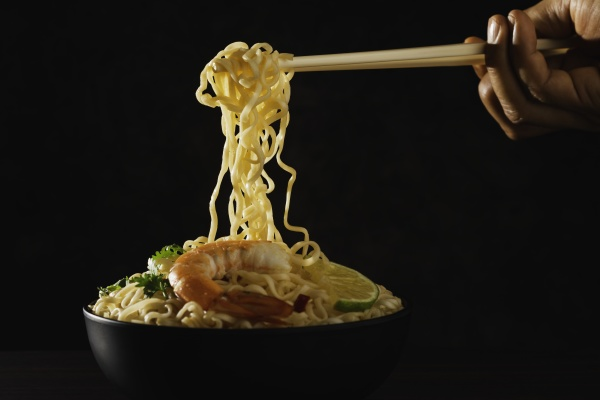 hand using chopsticks pickup instant noodles