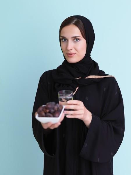 modern muslim woman in abaya holding