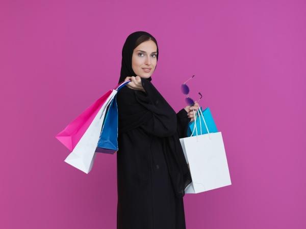 happy muslim girl posing with shopping