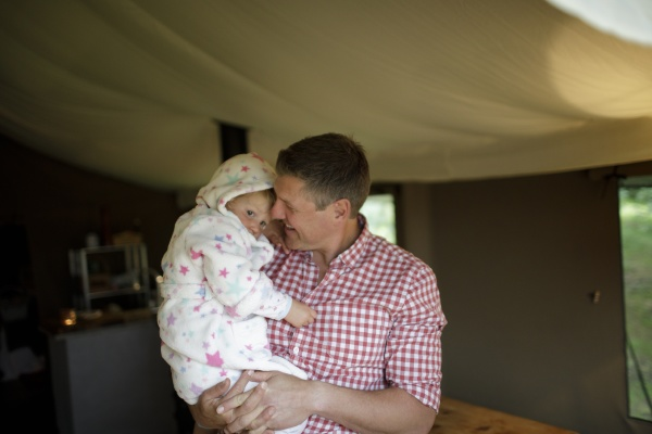 father holding cute daughter in bathrobe