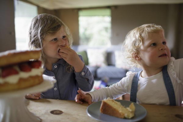 cute sisters eating strawberry cake at