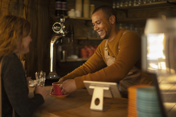 friendly barista serving coffee to excited