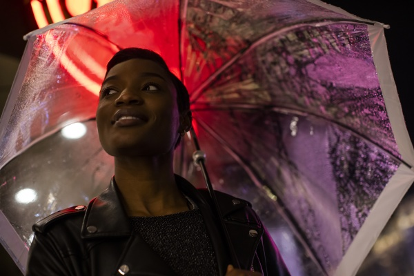 smiling young woman under umbrella and