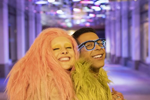 portrait happy stylish couple under neon