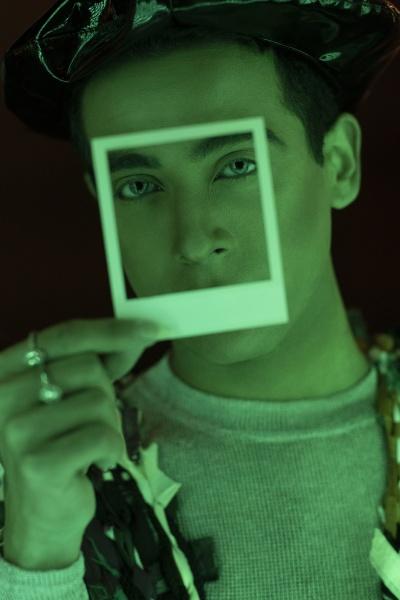 portrait stylish handsome man holding polaroid