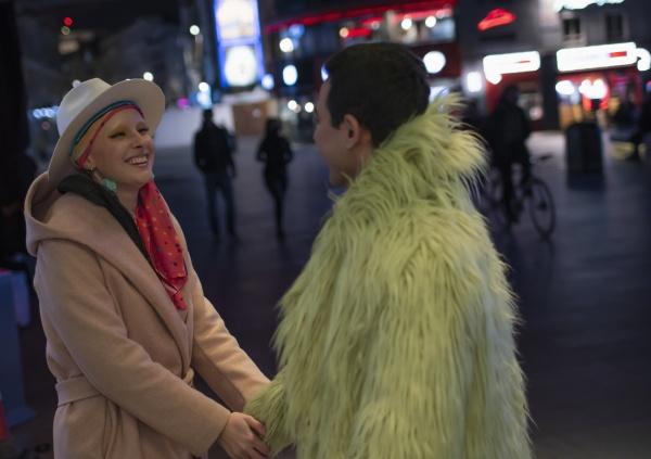 happy stylish couple holding hands on