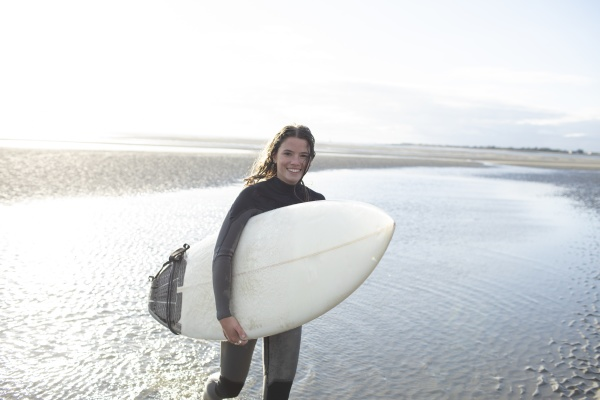 portrait happy young female surfer with