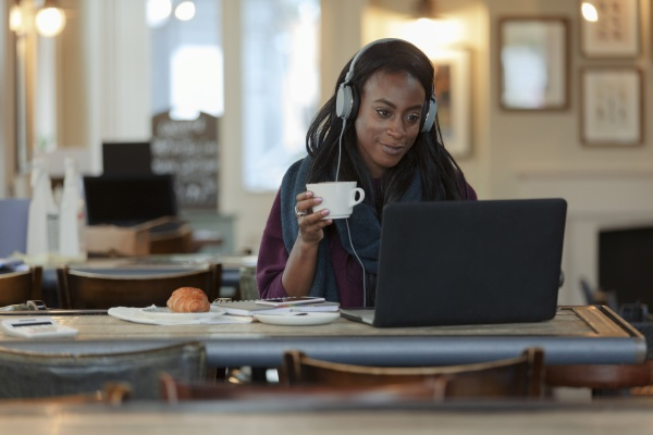 young woman with headphones drinking coffee