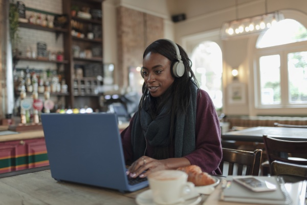 woman with headphones working at laptop