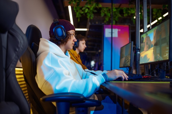 two young gamers in headsets play