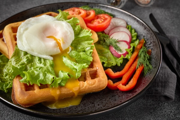 tasty waffles with poached egg and