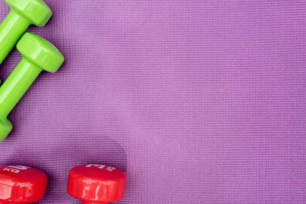 ladies dumbbells over purple fitness mat
