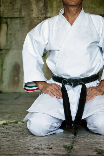black belt karate man sit on