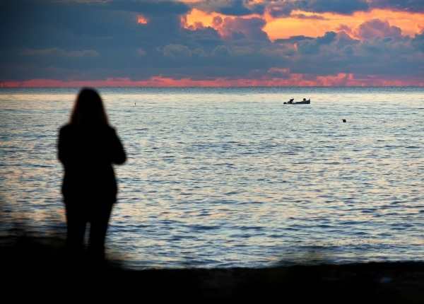 woman in silhouette observes the sea