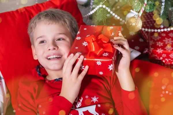 smiling blond boy holding festive gift