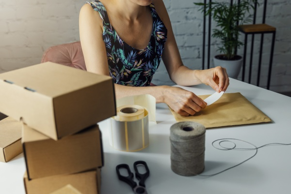 woman preparing parcel shipping label at