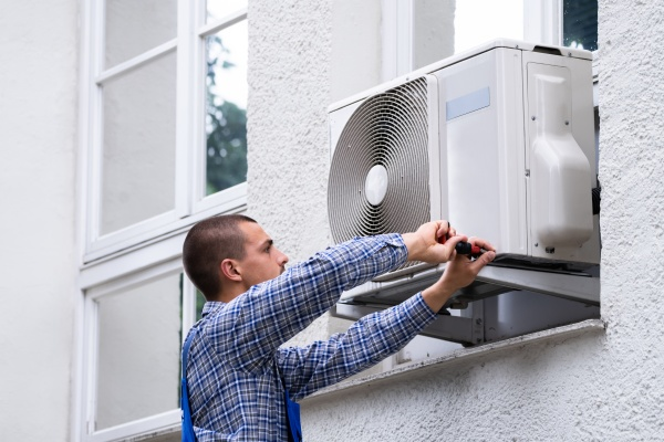 technician cleaning and repairing air condition