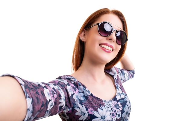 smiling young girl with sunglasses taking