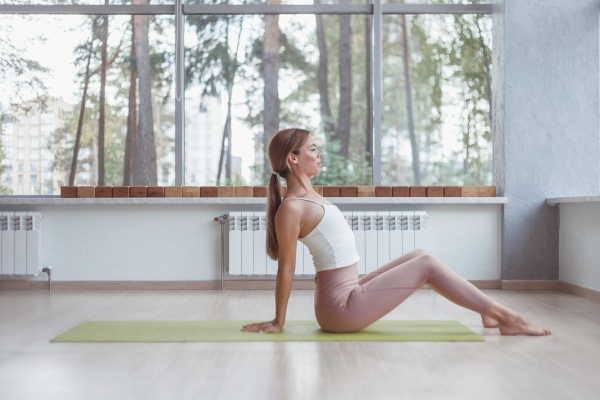 slim woman is stretching while sitting