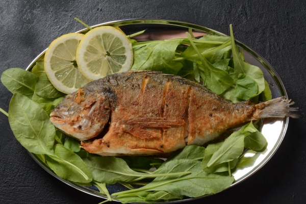 fried fish dorado with fresh herbs