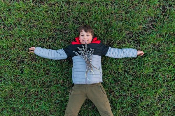 smiling teen boy lies on green