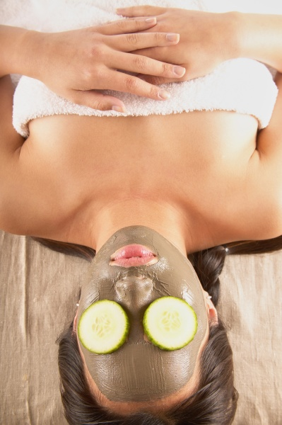 woman with mud mask and cucumbers