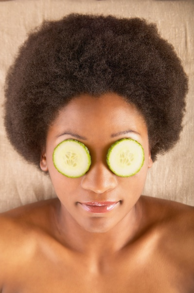woman with cucumber slices over eyes