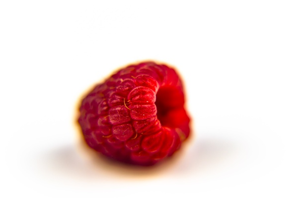 red raspberry berry on a white