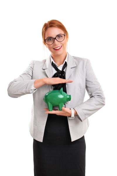 beautiful smiling businesswoman holding green piggy