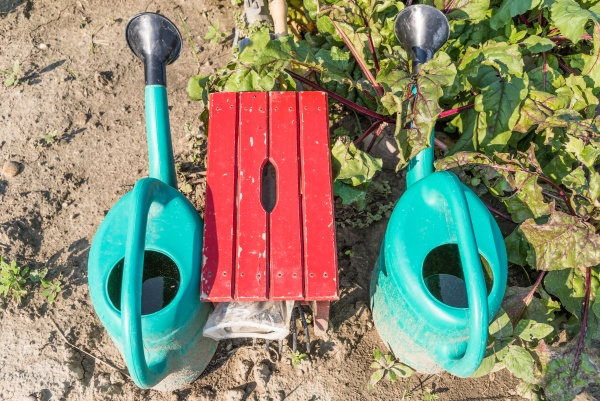 watering cans and stools in the