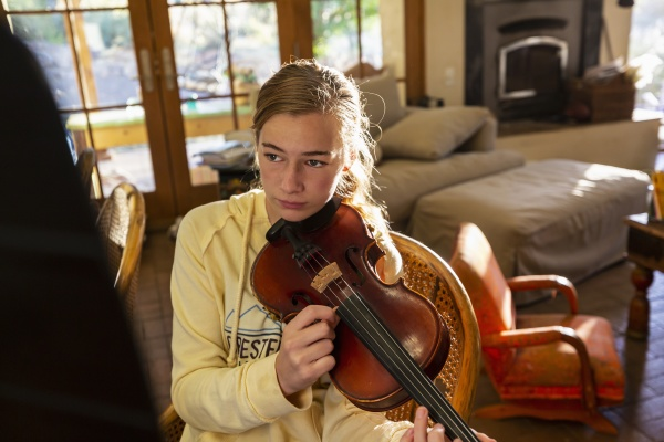 teenage girl plucking strings of her