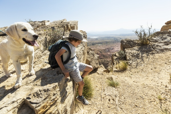 young boy hiking with his dog