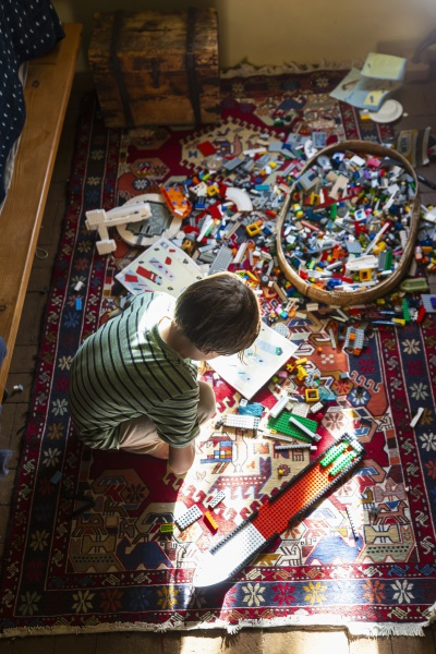 boy sitting among toys on his