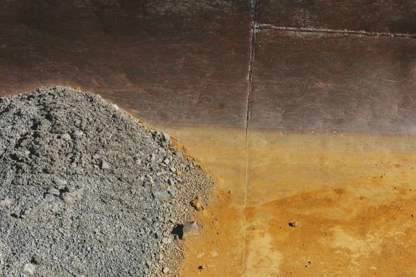 detail of rusty metal tank gravel