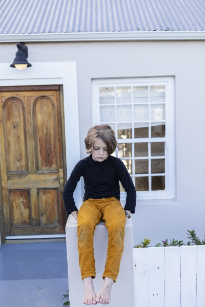 young boy sitting on a wall
