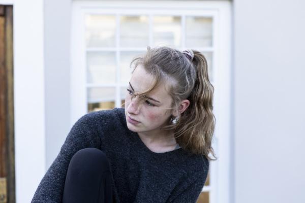 a teenage girl sitting outside a