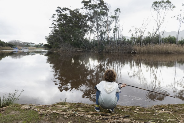 young boy sitting on a river