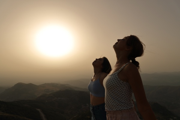 women silhouette breathing fresh air together