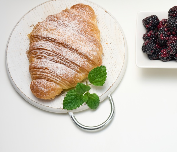 baked croissant sprinkled with powdered sugar