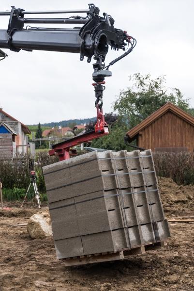 truck crane unloads building materials at