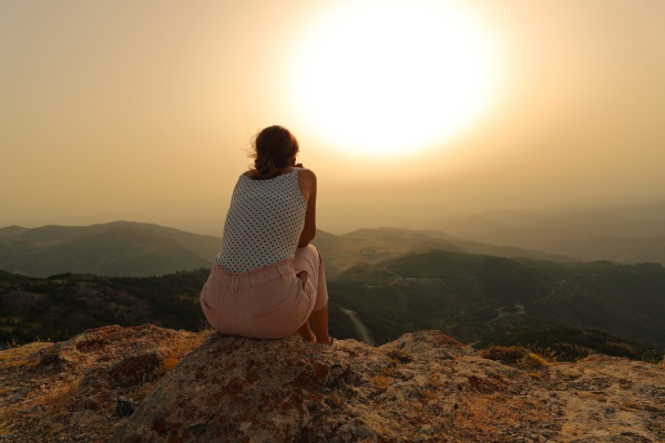 woman alone contemplating sunset in the
