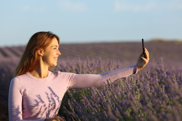 happy woman taking selfie with phone